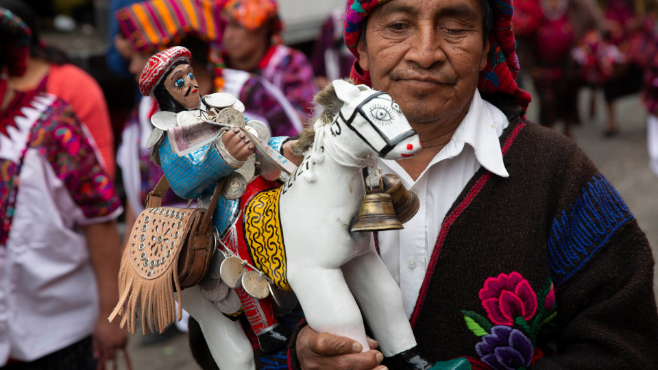 An indigenous spiritual guide holds an wooden statue of Saint Thomas, the patron saint of Chichicastenango, Guatemala, Saturday, Dec. 21, 2019. After eight uninterrupted days of celebration in honor of their patron Saint Thomas, fireworks accompany three bands that play simultaneously at the corners of one of the most emblematic markets in Guatemala. (AP Photo/Moises Castillo)
