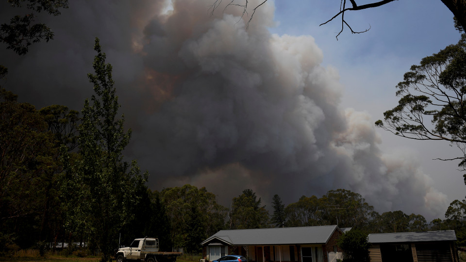"""A home stands as smoke from the Grose Valley fire rises in the distance in Bilpin, west of Sydney, Saturday, Dec. 21, 2019. Australia's most populous state has been paralyzed by """"catastrophic"""" fire conditions Saturday amid souring temperatures as wildfires also ravaged the country's southeast. (AAP Image/Dan Himbrechts) NO ARCHIVING"""